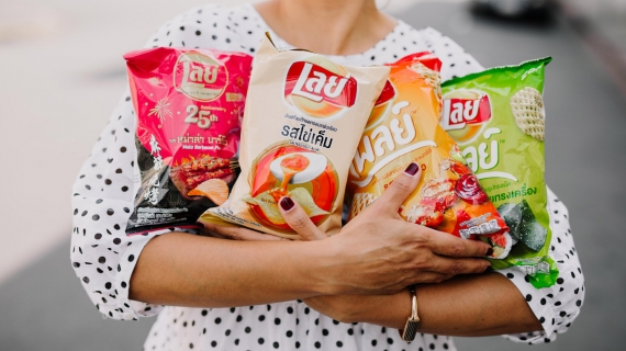 Woman holding four packs of savoury snacks